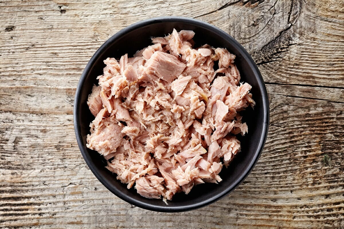 Bowl of canned tuna on wooden background top view