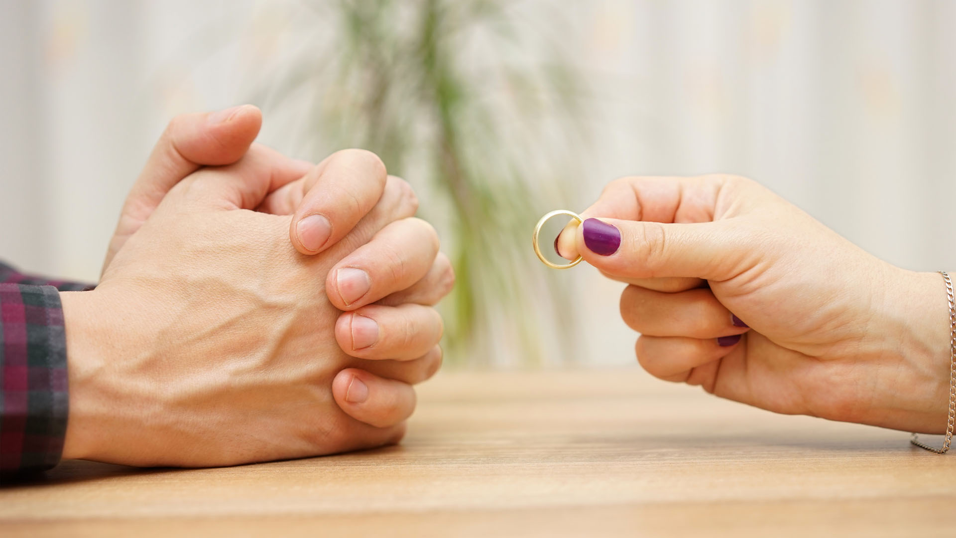 A womand handing back a ring to a man