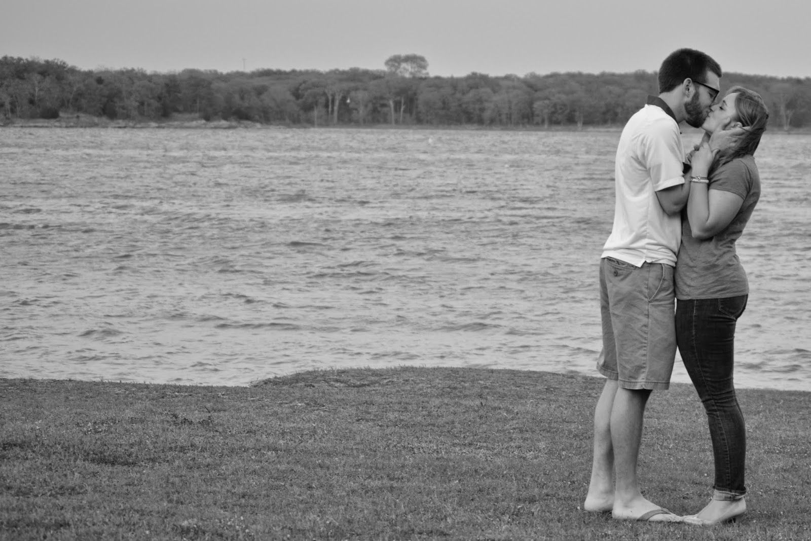 A black and white image of a couple kissing